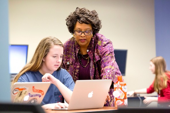 Barbara McCaskill helps English major Laura Essex with a project during her literary magazine editing class. Photo by Dorothy Kozlowski
